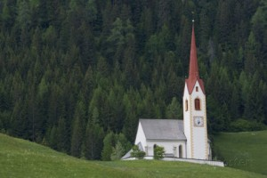 joe-petersburger-a-church-surrounded-by-pine-trees-in-a-hillside-meadow